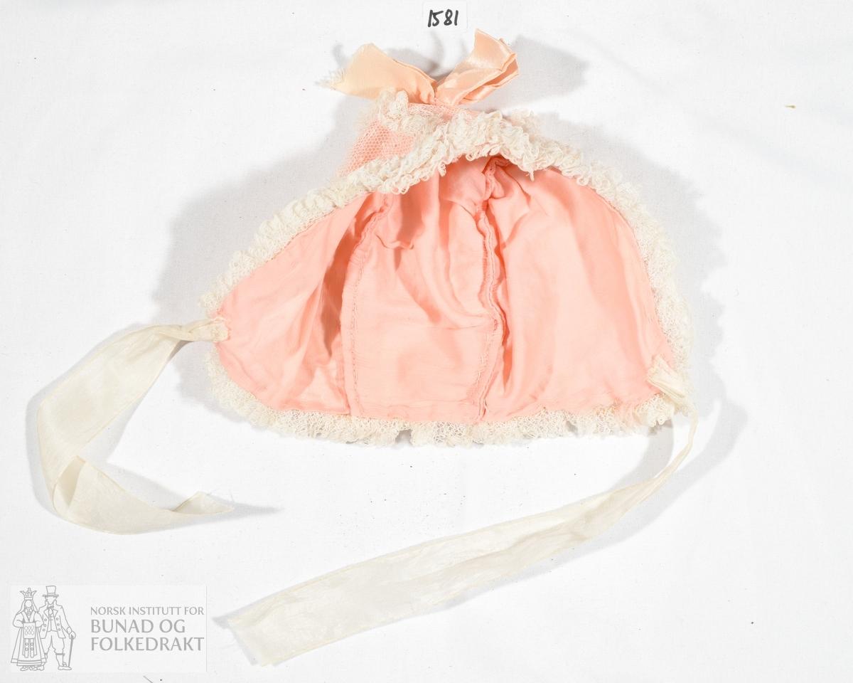 Barnelue i rosa bomullsstoff med ytterstoff av tyll. Sydd sammen på maskin. Blonder rynket sammen og nestet fast for hånd langs kantene og i sømmene.