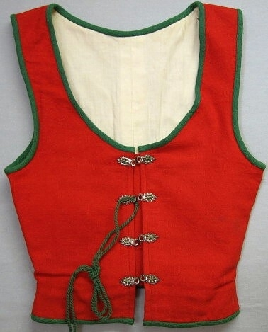 Livstycke i rött ylle, vävt i tuskaft. Kantat i ärmhål och runtom med grönt ylleband. Har ställskört bak. Har ett vitt linnefoder. Hopsnörningen sker med  4st snörmaljor på var sida, fastsydda med grön tråd. Snodden är av grönt ullgarn. Under snörningen sitter en röd  lapp. I framkant en korsettfjäder i var sida.