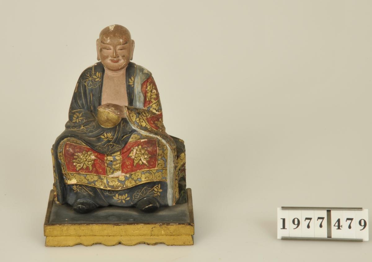 Sittande Buddha av trä, skuren i ett stycke och målad i flera färger. Monterad på en rektangulär platta av trä.