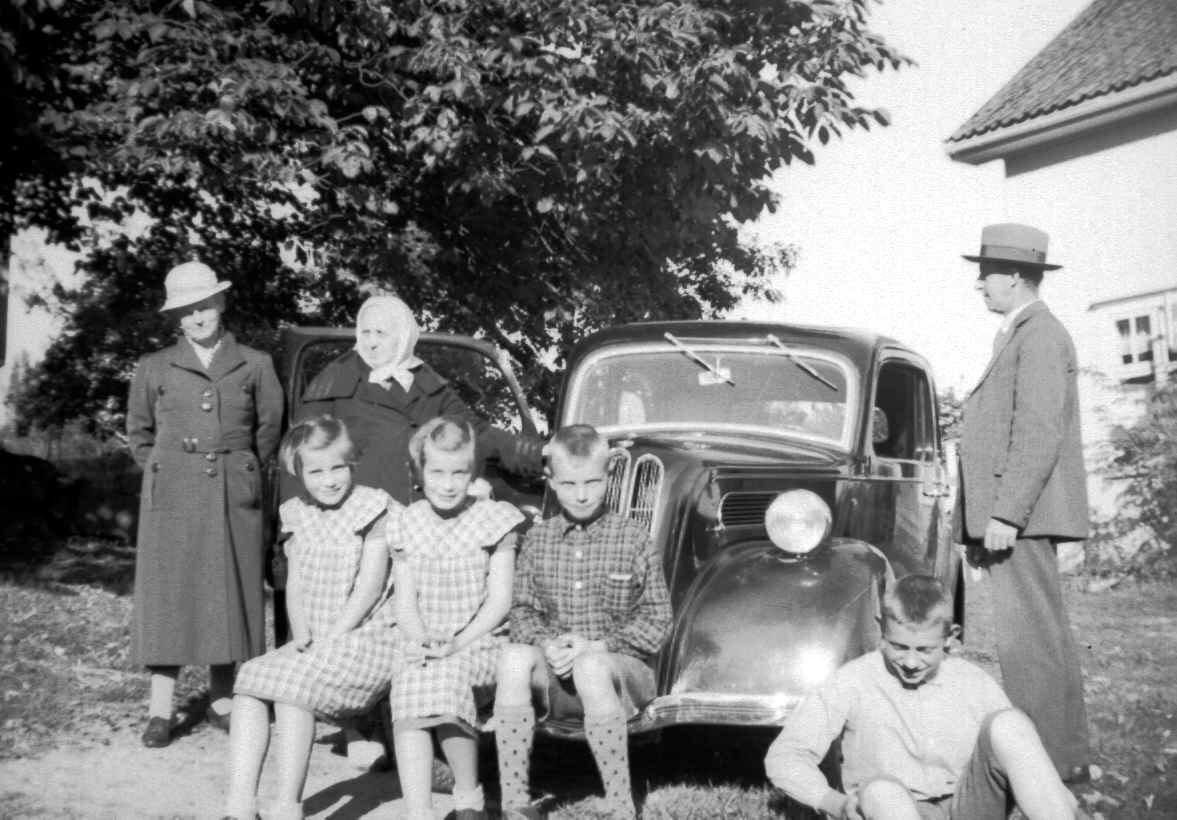 Familie samlet rundt bilen til August Bratteng på Jørstad søgard. Tvillingene Sigrun og Astrid Jørstad, f. 1930 foran til venstre på bilen. Stående fra venstre: Kari Bratteng f. Jørstad, Agnete Jørstad og August Bratteng helt til høyre