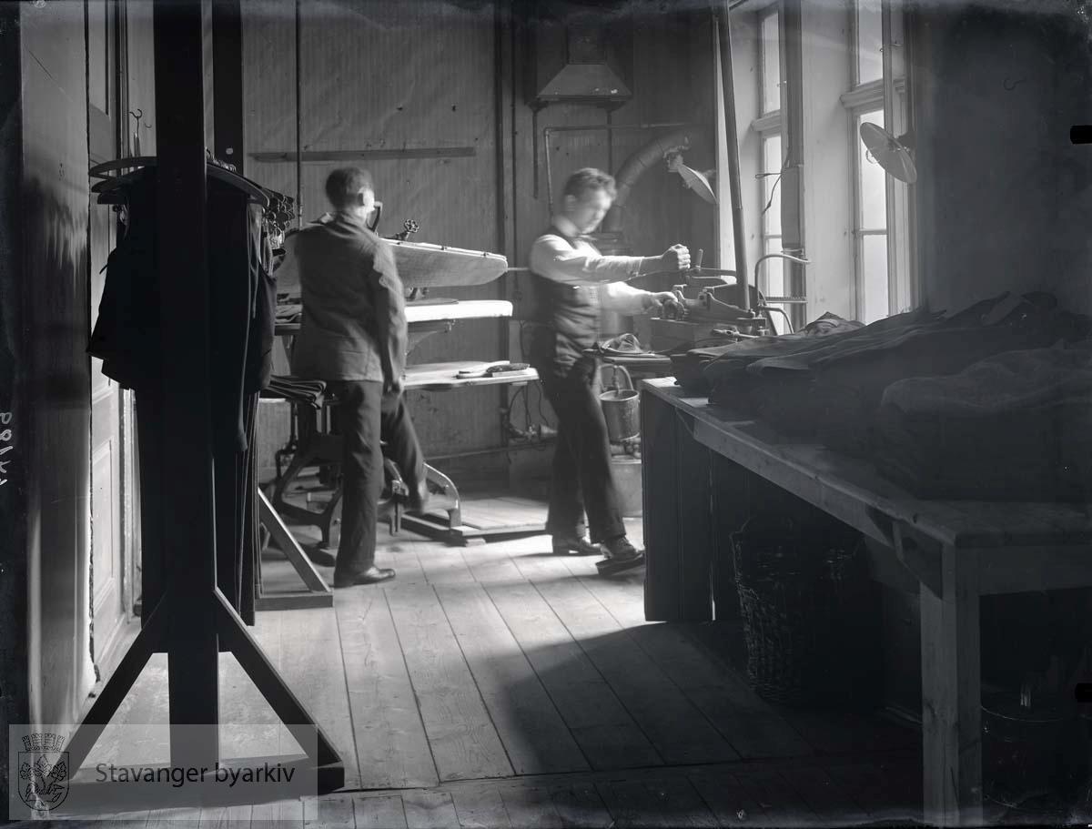 Interiør fra presseriet i K. Grudes fabrikk for finere herrekonfeksjon. To menn presser dresser. ..(Fotografens nr. 64189 er grunnlag for dateringen)