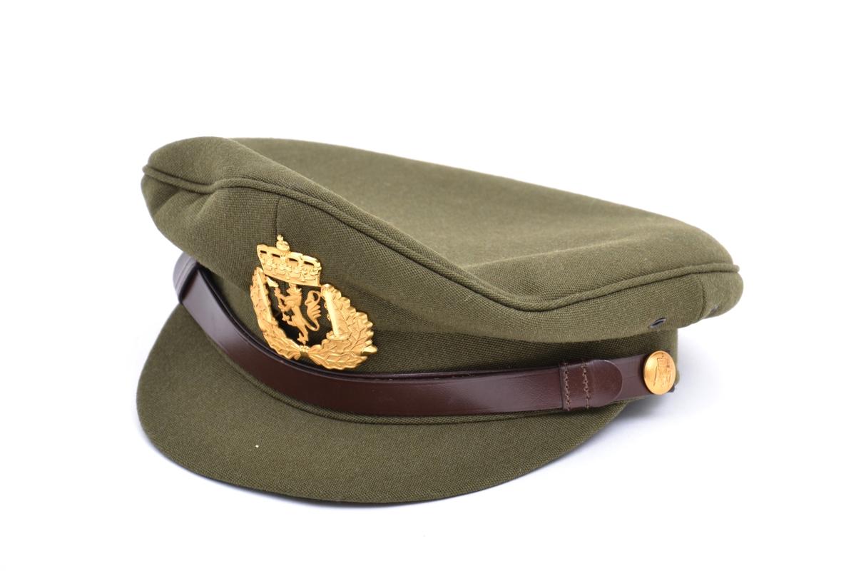 Uniformslue med skjerm og lærreim festet med gullknapper. Luemerke for hærens befal, sersjants grad laget av forgyllet metall. Merket er preget med hærens emblem med eikekrans.