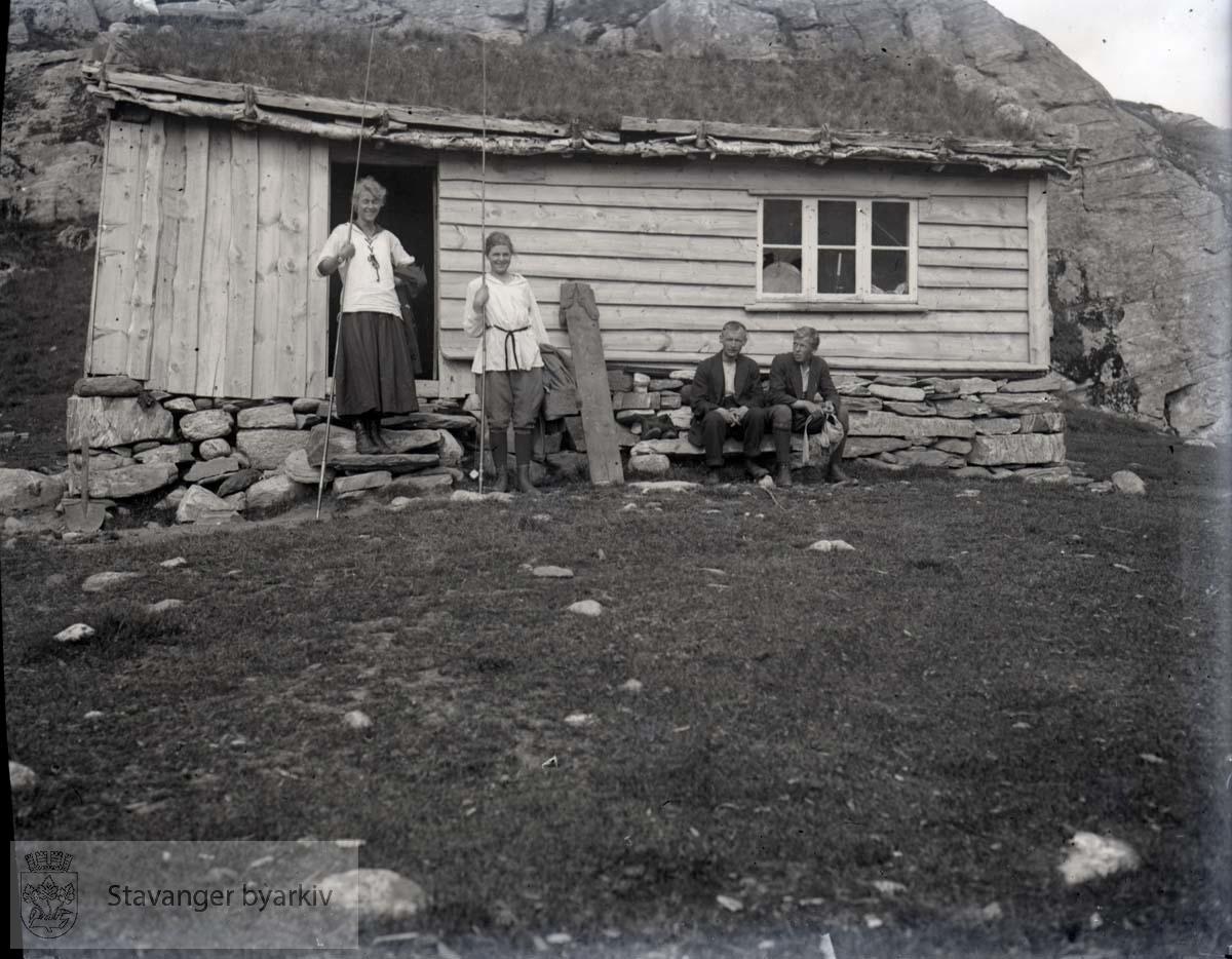 To kvinner og to menn utenfor hytte i fjellheimen