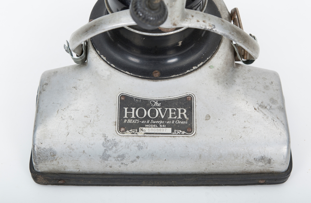 Elektrisk støvsuger.Motor og støvpose montert direkte på stang over sugemunnstykket.Stofftrukket kabel.