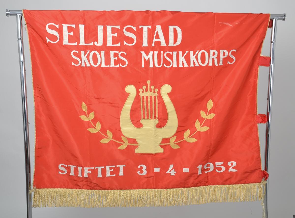 Fane i rød silke med gullsnorer, applisert og brodert med hvit og gul tråd.