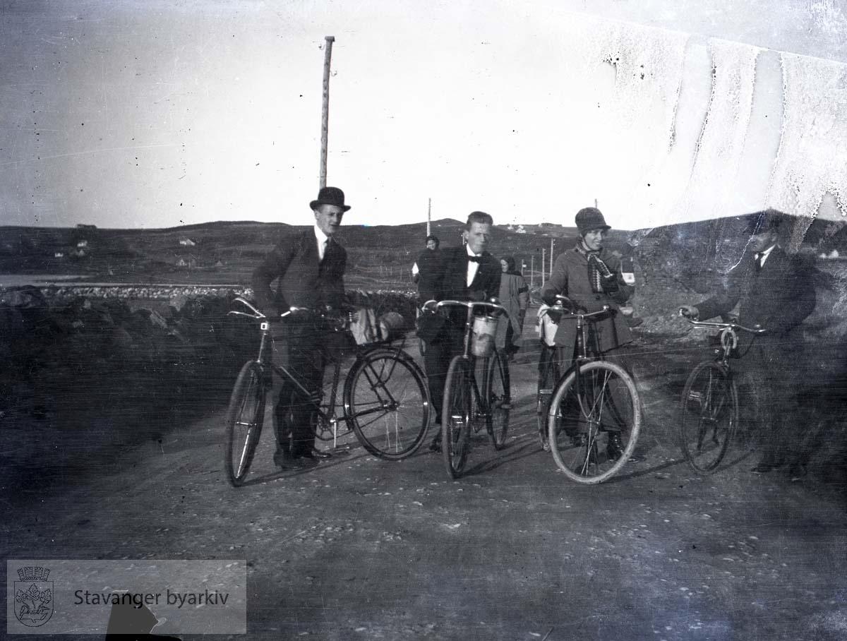 Tre menn og en kvinne med sykkel..Uvisst hvor.