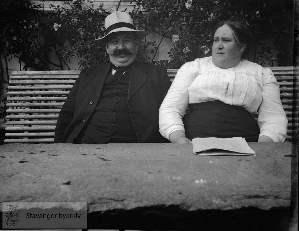 Par på benk i hagen.Muligens Jonas Pedersen og Olena Pedersen.