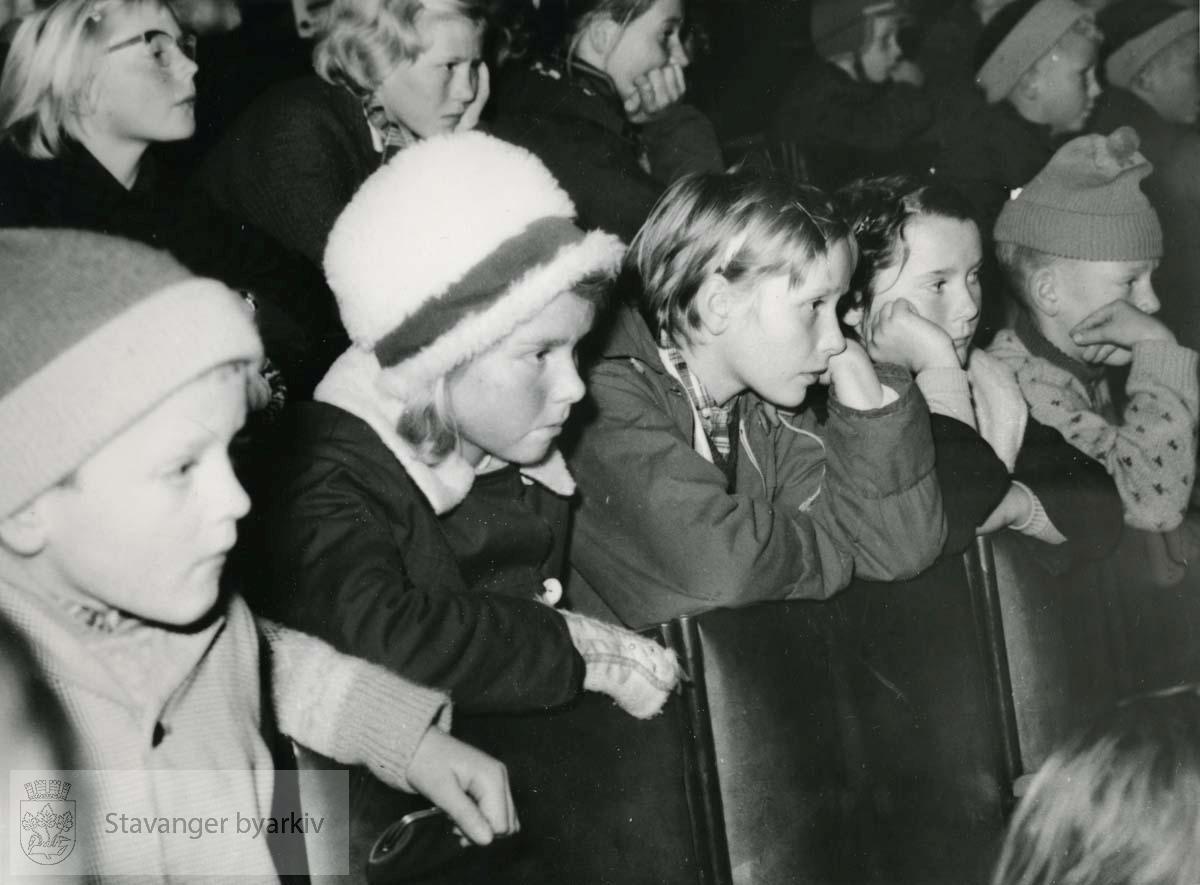 Barn i salen følger interessert med.