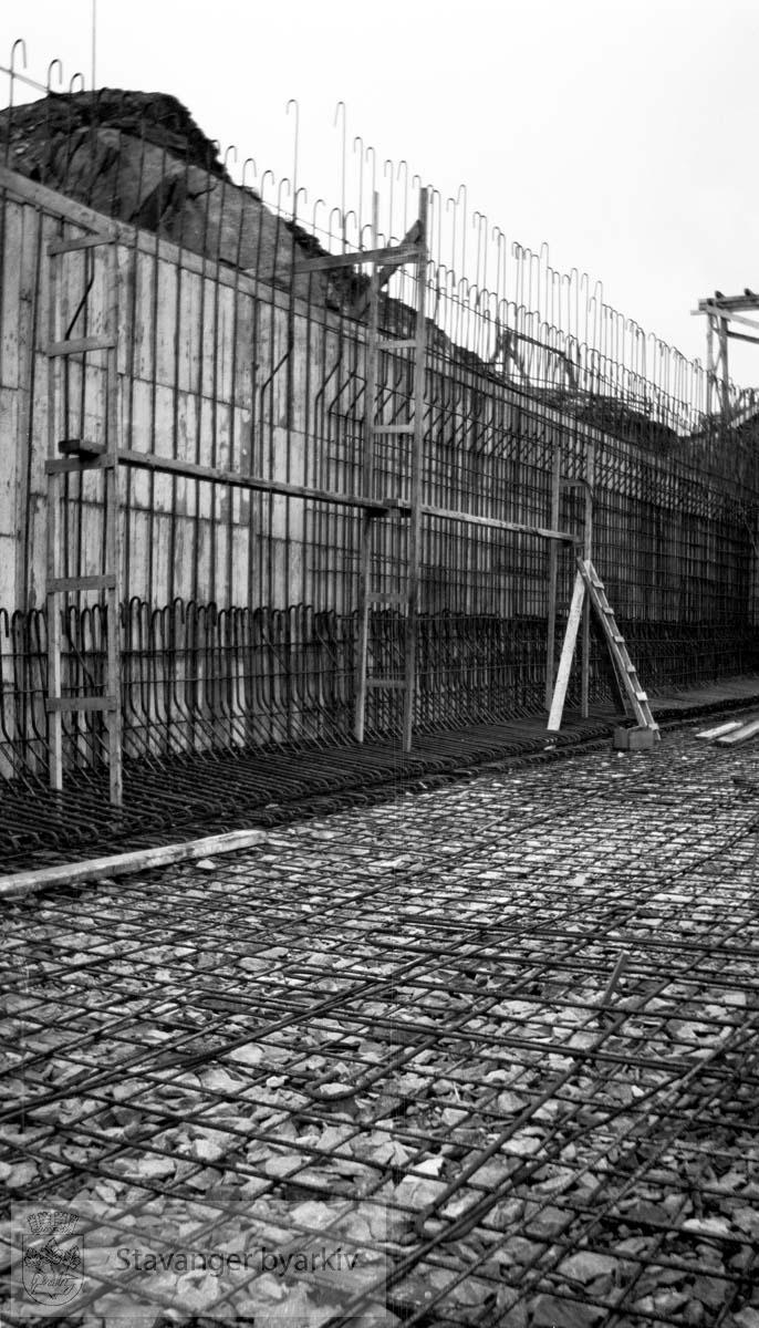 Armeringen i bassengveggene...Vann fra Store Stokkavatn ble pumpet opp til bassenget på Tjensvollhøyden 89 m o.h.Stokkavatnanlegget startet opp i 1930 og fra da stilnet pumpene i Egenes brannstasjon. Stokkavatnet var byens vannreservoar fram til 1959.