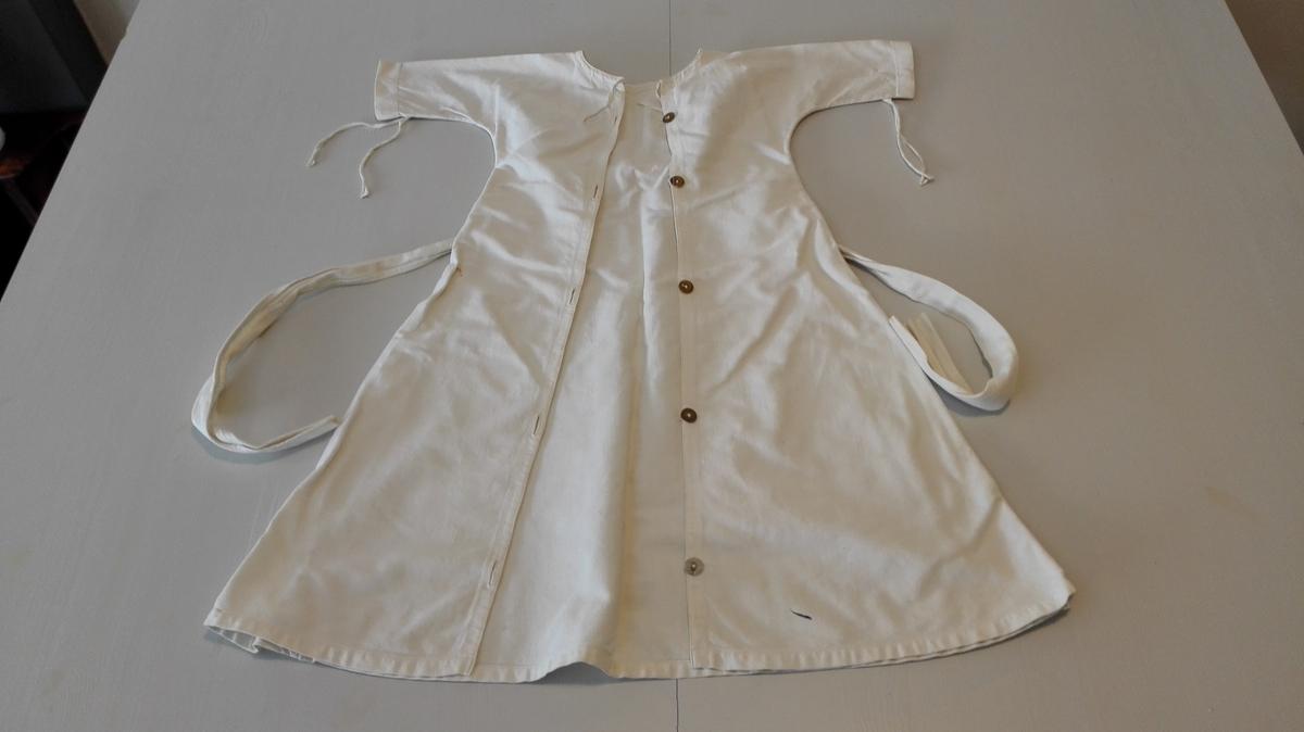 """B.forstk.:30cm, B.bakstk.:15cm, L.erme:23,5cm, V.nederst: 118cm. Sydd av diagonalvove bommullsstoff (bommesi). Heilklipt. Opning bak med 5 """"tøy""""knappar og knapphol. Løpegang m/bendelband kring utanpå skjorte, trøye og bleier. Merka med: PR 4. Brukt (sekundært) til stor dokke."""