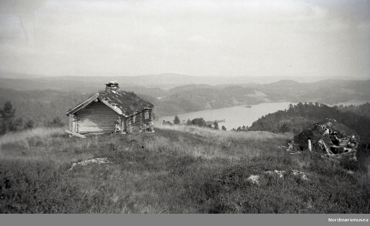 To falleferdige seterhus, ligg høgt i landskapet med utsyn over vatn.
