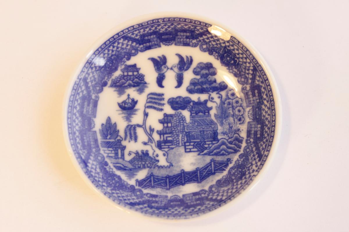 Blåvit kaffefat med kinesiskt landskap, pagoder, träd och fåglar. Tillhör dockservis