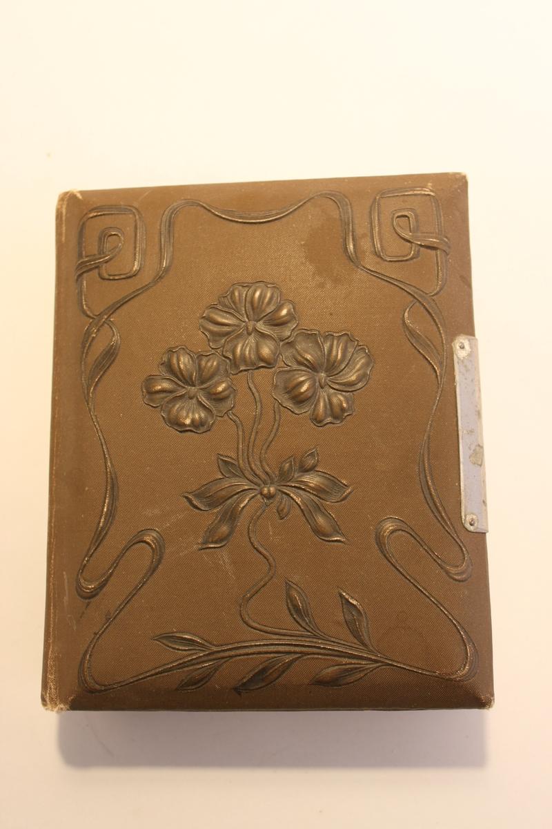 Brunt visitkortsalbum. Framsidan dekorerad med girlander och blommor i relief. Fylld med porträttbilder sk visitkort. Blilderna är från sekelskiftet 1900.