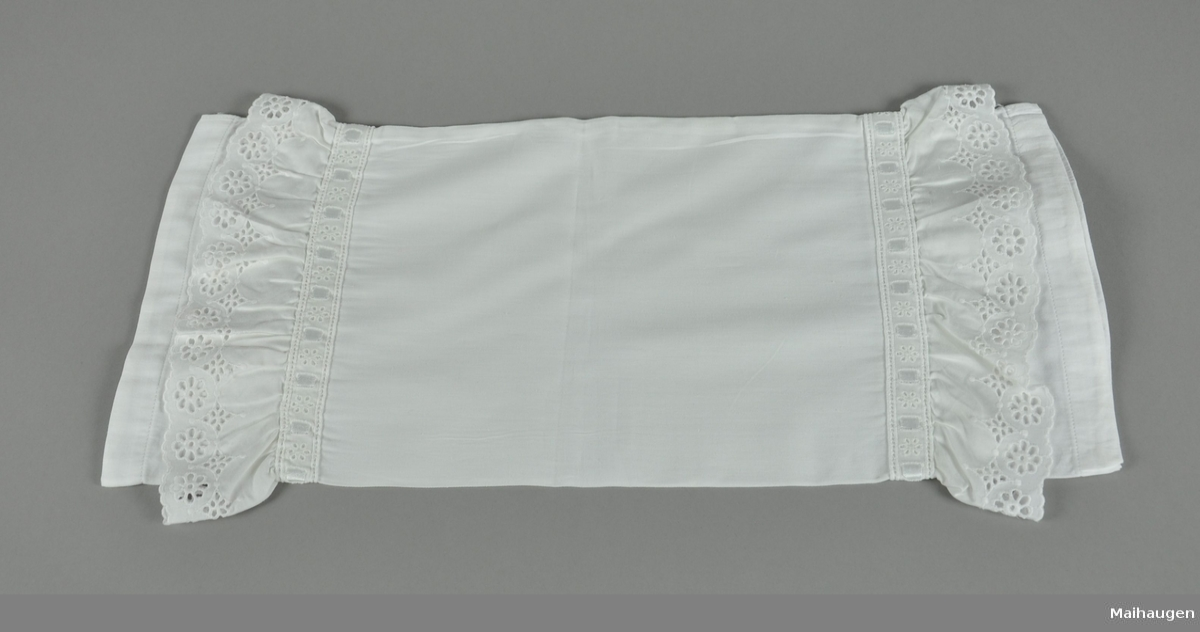 Hvit tekstil, rektangulær form. Putevaret har blonder ved kortendene.