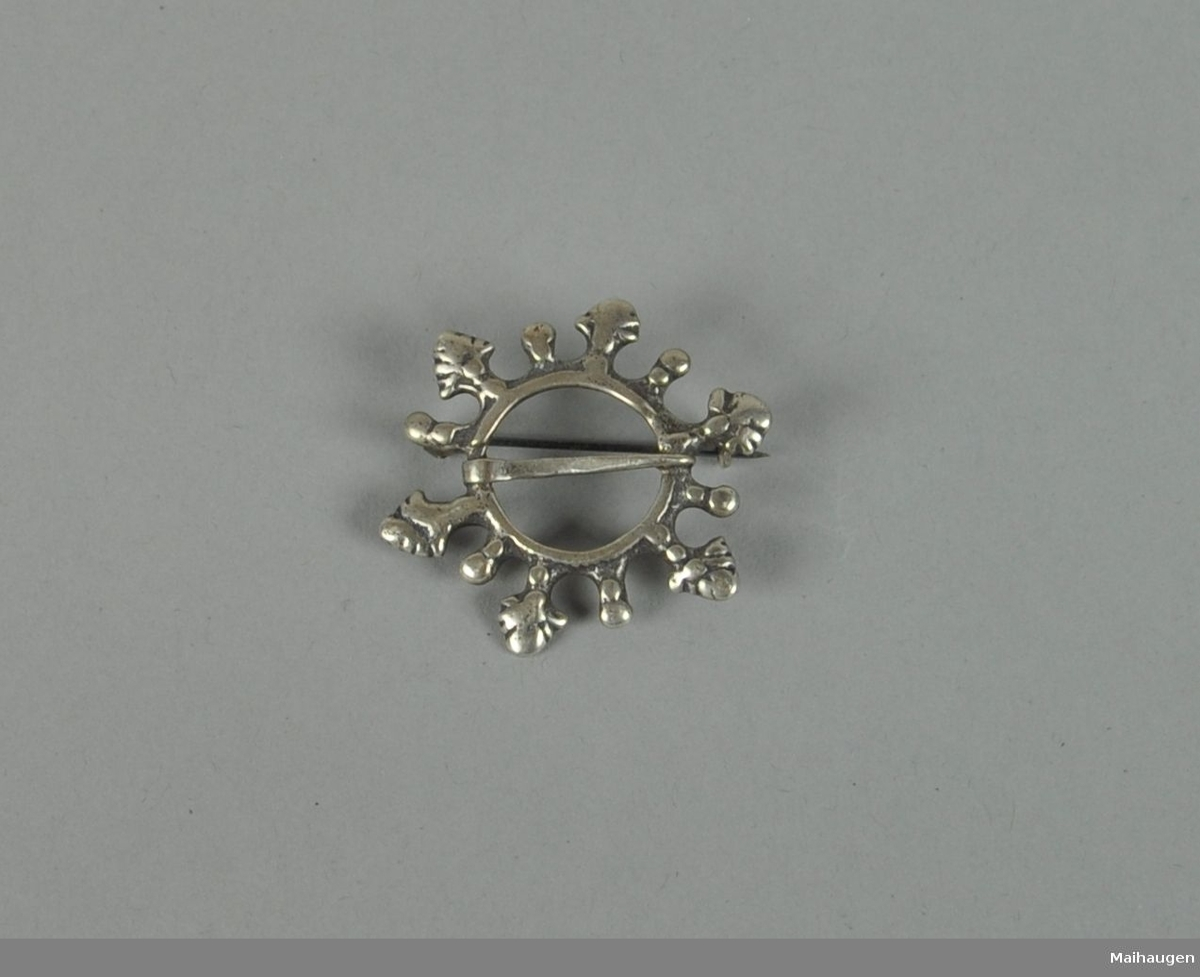 Rund brosje av sølv med seks store og seks små tagger.