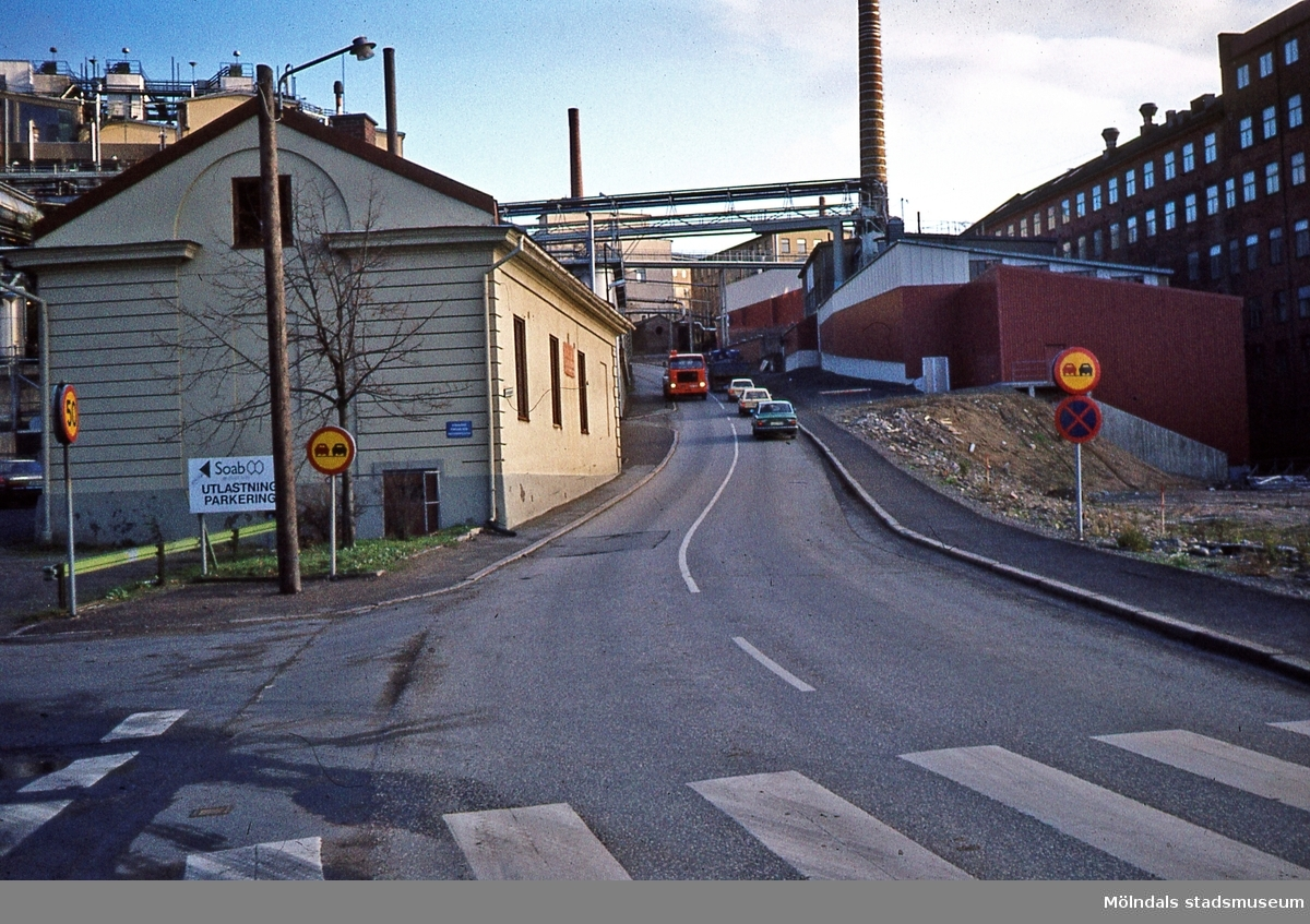 """Trafik i backen """"Kråkan"""" som är en del av Kvarnbygatan i Mölndals Kvarnby. Okänt årtal. Fotografi före ombyggnaden. Till vänster om gatan ses Götiska Förbundets friskola. Till höger ses industribyggnader tillhörande Soab samt byggnaden Stora Götafors. D 37:31."""