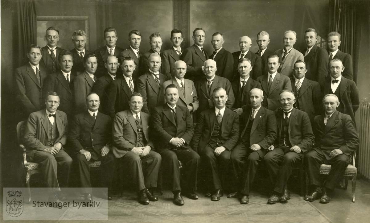 Bakerste rekke: M. Haga, E. Hellesøy, E. Skjørestad, T. Malmin, S.T. Årtun, E. Nygård, K. Løyning, P.O. Løvås, E. Valheim, A. Stensland, O.P. Haugstad, T. Østbø, K. Bjørnø..Midtre rekke: T. Heggebø (sektretær), H. Kjønås, R. Birkeland, Edv. Helgeland, T. Lie-Bjelland, T. kommedal, M. Wølstad, T. Lye, L. E. Larsen, N. Ågesen, M. Hellevik, L. Lie..Foran (formannskapet): O. Hetland, J. I. Østbø, O.O. Tjensvold, O. Tveterås (ordfører), J. Askeland (varaordfører), J. Larsen, T. Molaug, E. Frøiland