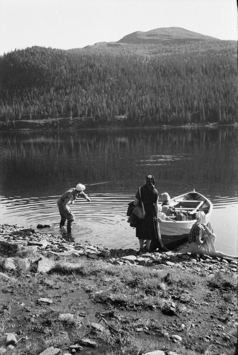 Robåt med folk ved bredden av Espedalsvatnet