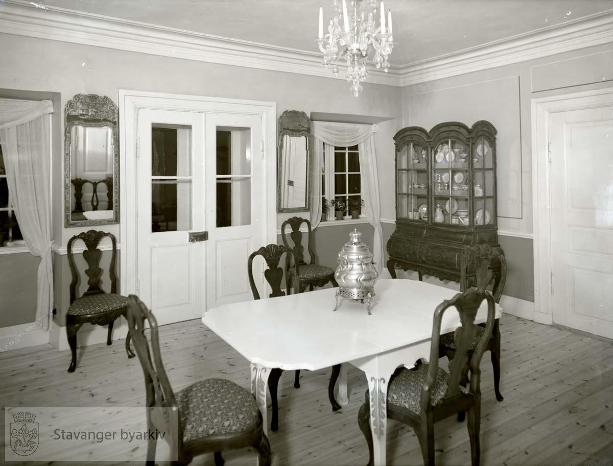 Hagestuen med stoler og bord, vitrineskap,speil og samovar.