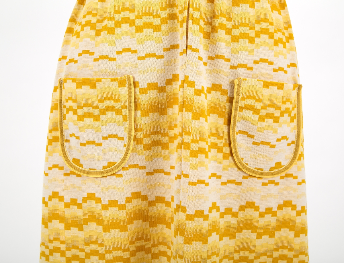 """Kjole fra slutten av 1960 tallet. Monstret i gul og hvit med belte med 2 knapper. Korte ermer. To lommer. Glidelås foran. Snipp.  """"Kjoler fra slutten av 1960 tallet. Etter jeg begynte å jobbe i 1968. Helt klassiske for hva som var moderne på den tiden. Husker at kjolene er fra min tid i Oslo. Desverre finnes det ikke bilder av meg med disse klærne."""" Tidligere eier"""