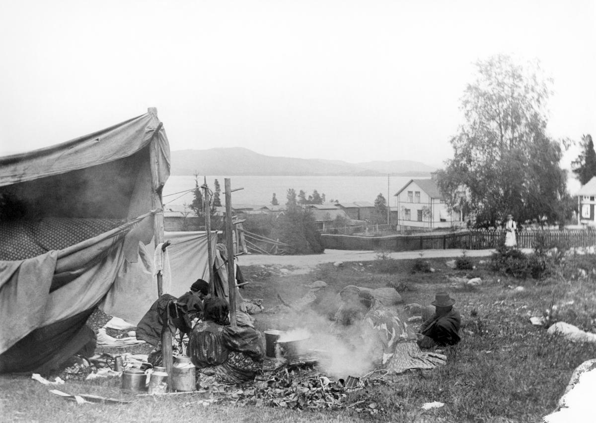"""Här syns ett romskt sällskap som slagit läger i en grässlänt. Bilden är troligtvis tagen kring sekelskiftet 1900, men platsen är okänd. Vid 1800-talets slut började romer från Sydeuropa i högre grad att resa runt i hela Europa för att idka handel och arbeta med hantverk. På 1860-talet avskaffades slaveriet av romer i Valakiet (ung. dagens Rumänien och Moldavien). De förslavade romerna talade valakisk romani, främst lovari, kelderash och tjurari. Efter slaveriets avskaffande sökte sig många av de befriade till resten av Europa, men även till Amerika, Asien och Australien. Denna folkvandring sägs ha pågått fram till första världskriget. I Sverige kom den dock att begränsas till följd av inreseförbudet för romer som infördes år 1914. Efter ankomsten av valakiska romer till Sverige börjar majoritetssamhället göra skillnad på skandoromer och valakiska romer. De föregående kommer då att kallas """"tattare"""" medan de senare kommer att kallas """"zigenare"""". Tidigare användes dessa benämningar synonymt. Dessa epitet uppfattas idag som kränkande. Efter att Sverige år 2000 anslöt sig till Europarådets konvention om skydd för nationella minoriteter, så börjar ättlingar till de valakiska romerna att kallas för """"svenska romer"""" medan ättlingar till skandoromer övergripande betecknas som """"resande""""."""