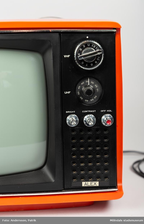Liten röd bärbar tv med 11 tums skärm av märket ALEX. Tillverkad under 1970-talet. Apparatens ytterhölje är av röd plast. Den har två större vred på vänster sida om skärmen, att välja tv-kanal med. Samt tre mindre vred att ställa in ljus, kortast och volym med. På ovansidan finns ett utfällbart handtag att bära TV:n med.