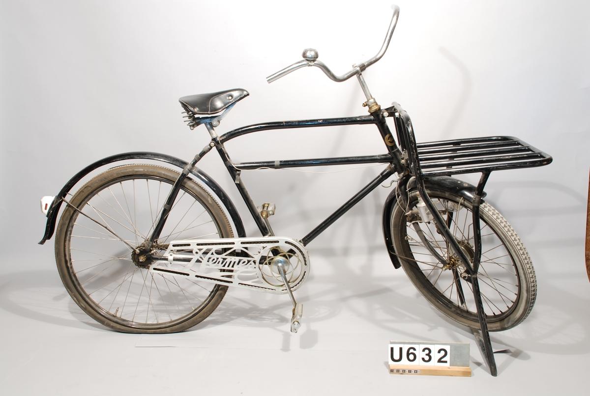 """Paketcykel, Crescent. Herrmodell. Text på kedjeskyddet: """"Hermes"""". Transportcykel, Crescent, svartlackerad med förstärkt övre ram, något svängd. Pakethållare med parkeringsstöd (55X40) fram. Hjuldiameter: fram 24X2 bak 26X2. Belysning: Bosch. Kedjeskydd: Hermes. Fram- och baknav nya, identiska med originalen, ny originalsadel och nya pedaler. Framhjulet har bromstrumma, som ej är inkopplad. I användbart skick."""