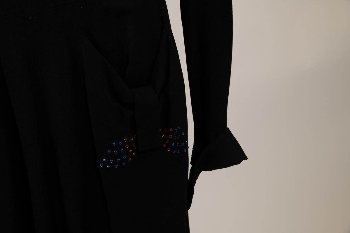 Sort kjole med blå og røde strass-steiner i plast. Skjørtet er overskåret i livet, og sterkt utskrådd nede ved hjelp av mange trekantede kiler. To lommer drapert med et vertikalt bånd og pyntet med røde og blå paljetter. Livet foran har midtsøm og skråsøm med legg over brystene. Hjerteformet krage med paljetter. Lange meget smale ermer, som går ut i spiss nederst. Ryggen har to silketrukne knapper til livet. og glidelås nedenfor livet.