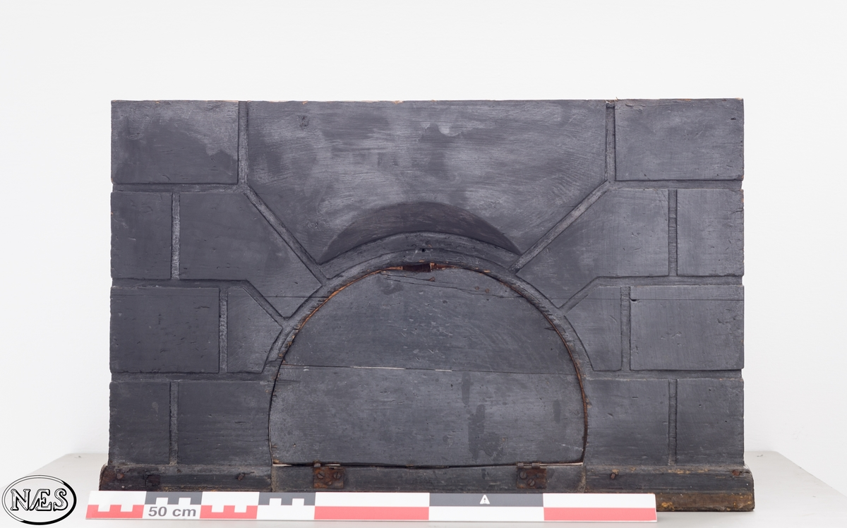 Firkantet ovnskrakk i heltre. De fire sidene er festet sammen ved hjelp av svalehaleskjøt i hjørnene. tre av sidene har innskåret et symetrisk mønster i overflaten - arkitektoniske element. Front og bakplate på ovnskrakken har en rundbuet åpning. Åpningen i front har en luke.  Ovnskrakken avsluttes med en glatt sokkel mot bakken.
