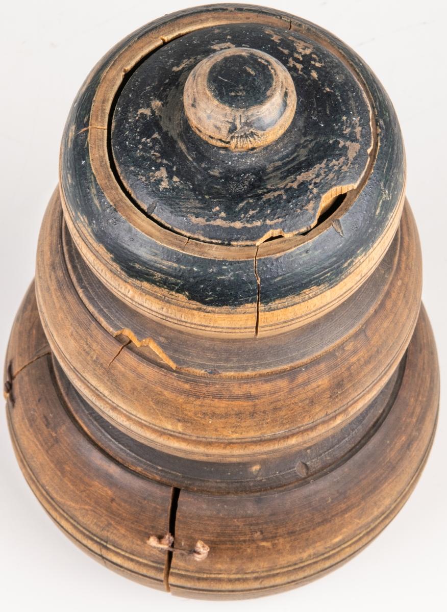 Svarvad kryddosa i 3 våningar. Skruvas isär. Inuti bläckinskrift, bland annat 1843. Spår av blå färg på dosans övre del. Nedre dosan sprucken och lagad med ståltråd och snöre.