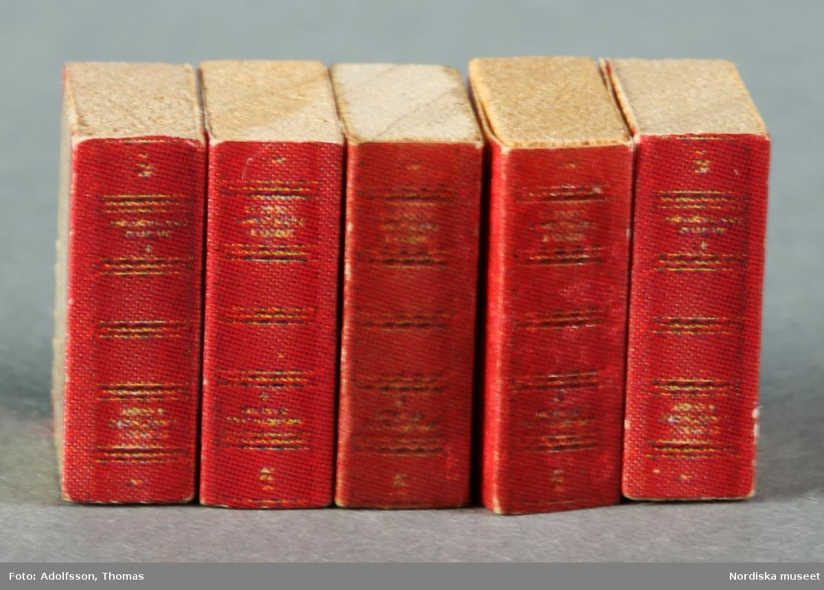 Fyra hemsnickrade bokhyllor av masonit och trä. Brunmålade. Innehåller 61 böcker av papp, trä och plast och 6 attrapper av trä som också föreställer böcker. På översta hyllan står prydnadssaker som kannor, ur, byst och jordglob. Hyllorna står längs väggarna i biblioteket på andra våningen i dockskåpet.