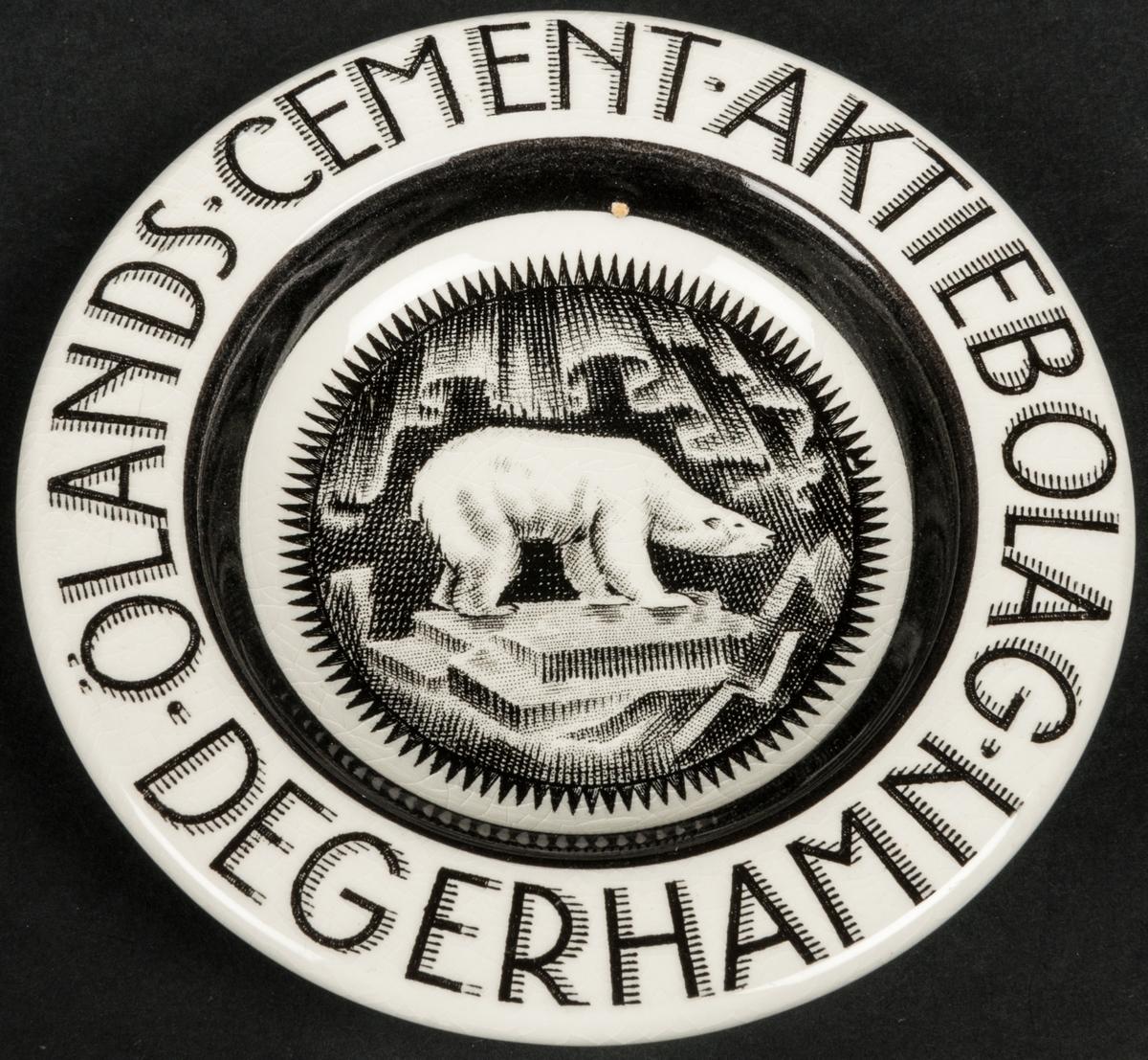 Askfat, vitt med svart dekor av isbjörn i botten. Runt brämet: Ölands Cement Aktiebolag Degerhamn.