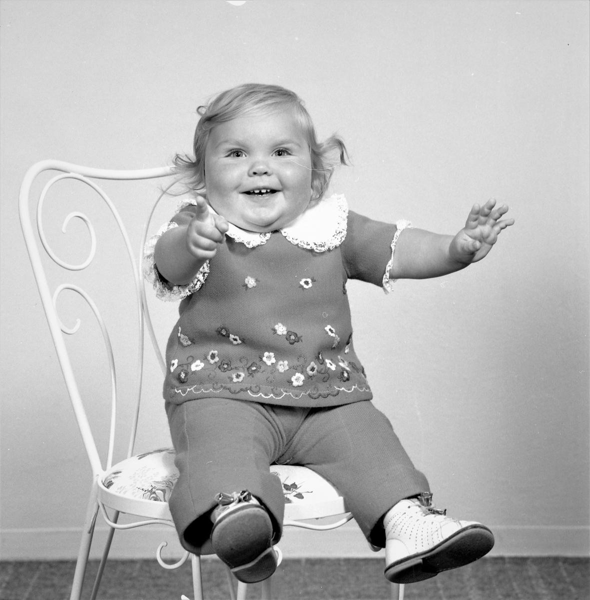 Portrett. Liten lyshåretpike i kort farget kortermet bluse med blomstermotiv langs nedre kant, lys pynt på ermene og stor lys krage. Fargede bukser og lyse sko. Bestilt av Karen Endresen. Kirkegt. 190