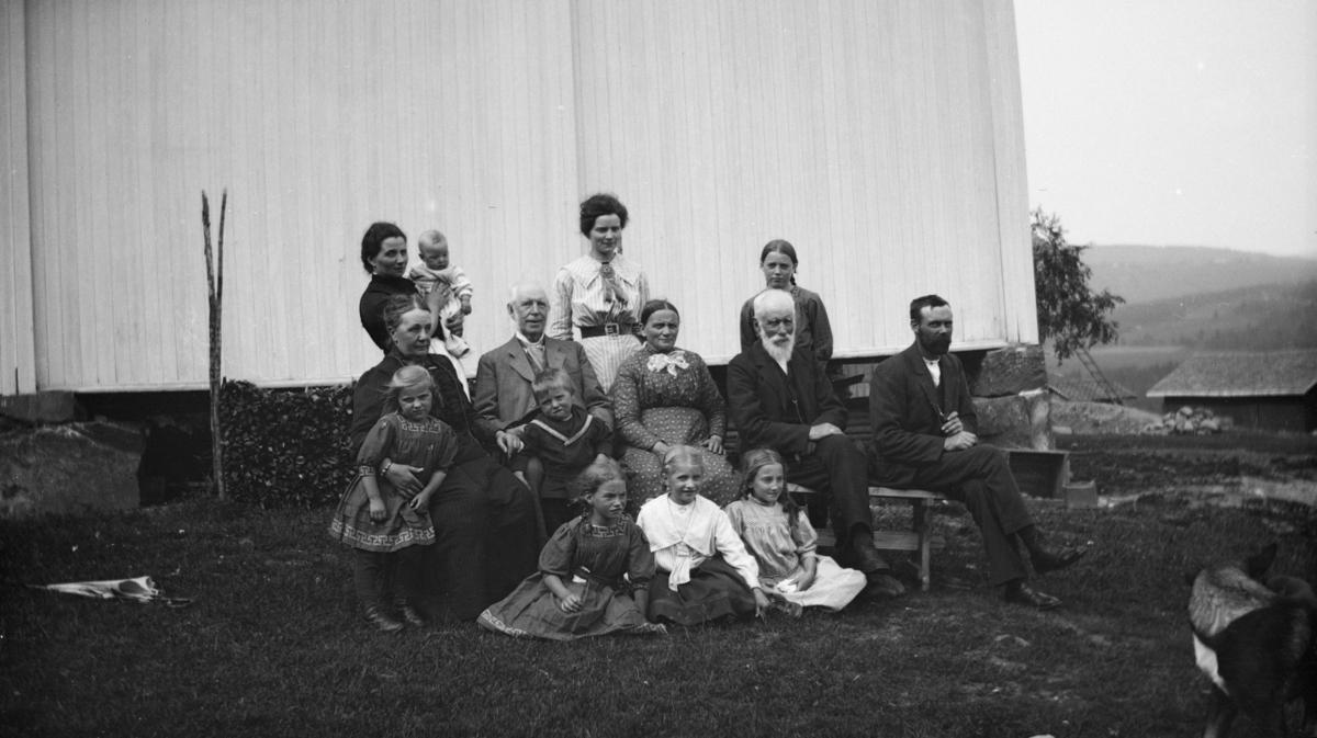 Familiebilde av 14 unge og eldre, på ukjent gårdsbruk