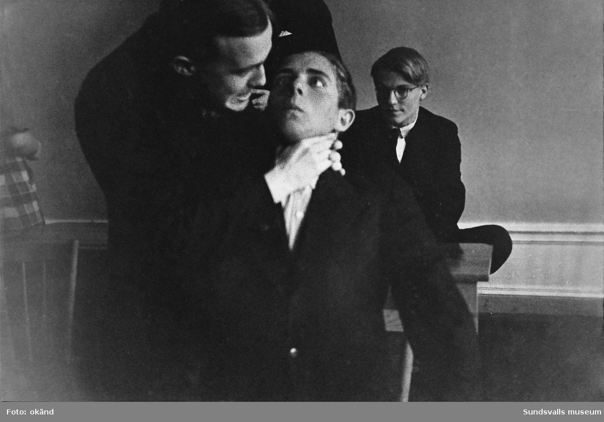 """""""Studentexamen 1937 vid Sundsvalls högre läroverk började med svensk skrivning. Innan vi gick till skolan samlades vi vid Bewe's hörna (Storgatan-Torggatan). Där släppte var och en av oss en ettöring från födelseåret ner i dagvattenbrunnen. Därefter gick vi till skolan med en fot i rännstenen och den andra på trottoaren så lång det gick."""" Bild 2 Fr v Lennart Uhlin, Ture Engblom och Martin Löfgren. Bild 6 Betygen studeras. Fr v Liljekvist, Curt Stål, L M Thuresson samt okänd. Bild 8 Numrerade personer. 1. okänd 2. L. H. Thuresson 3. okänd 4. Thure Engblom 5. okänd 6. Martin Löfgren 7. Lundgren (?) 8. Curt Stål 9. G-A Wahlsten 10. Ingemar Flodén 11. Anna-Lisa ? 12. Nilsson (lärare) 13. Maidi Budde 14. Lennart Uhlin 15. Harald Schibbye.  Bilder ur fotoalbum som tillhört G A Wahlsten."""