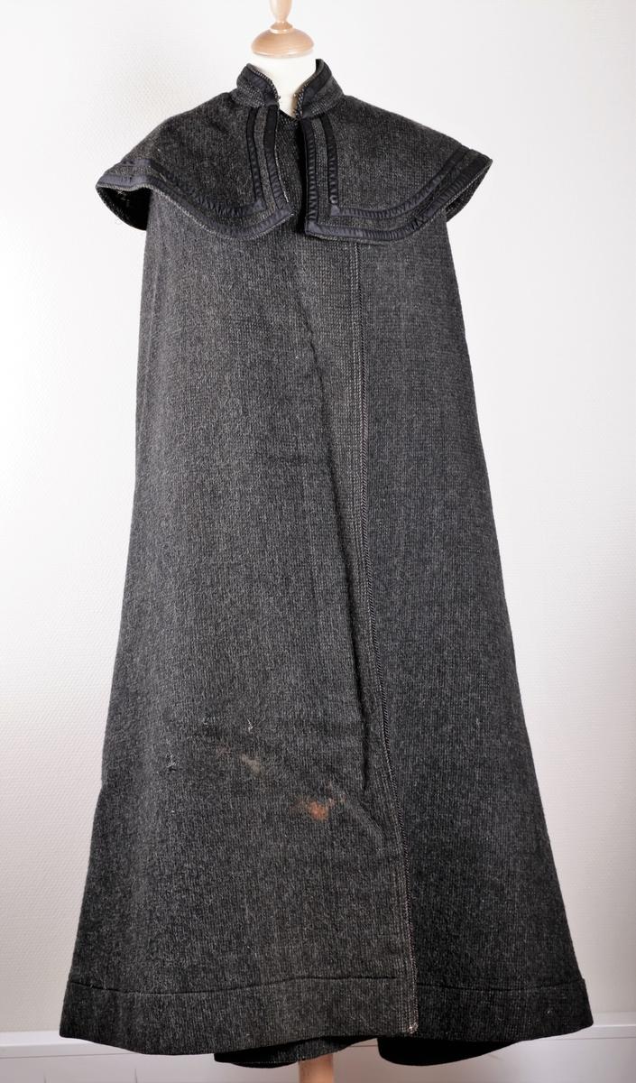 Kappe i tjukt ullstoff. Lang, med stor krave som er kantet med pyntebånd i svart. Stoffet er grått og svart stripet på retten, og svart og kvitt rutet på vrangen.