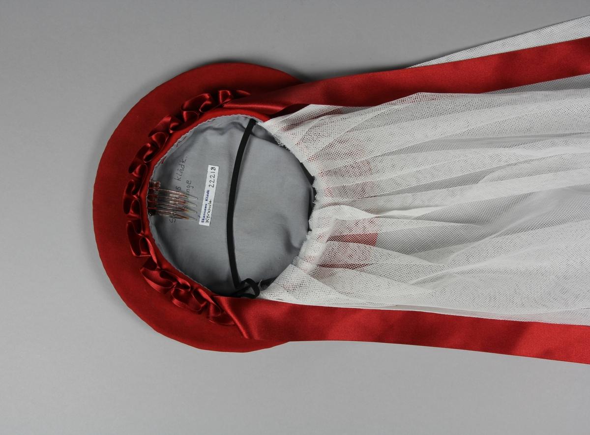 Huvudbonad av röd ull med hård stomme. Platt tallriksliknande modell med liten upphöjd kant. Tillverkad genom ändring av en befintlig huvudbonad på Skansens klädkammaren, för att efterlikna originalet NM.0003649 i Nordiska museets samling. Längs kanten ett satinband av polyester, originalet är troligen i siden. Under huvudbonaden hänger en tvådelad slöja i bomullstyll.