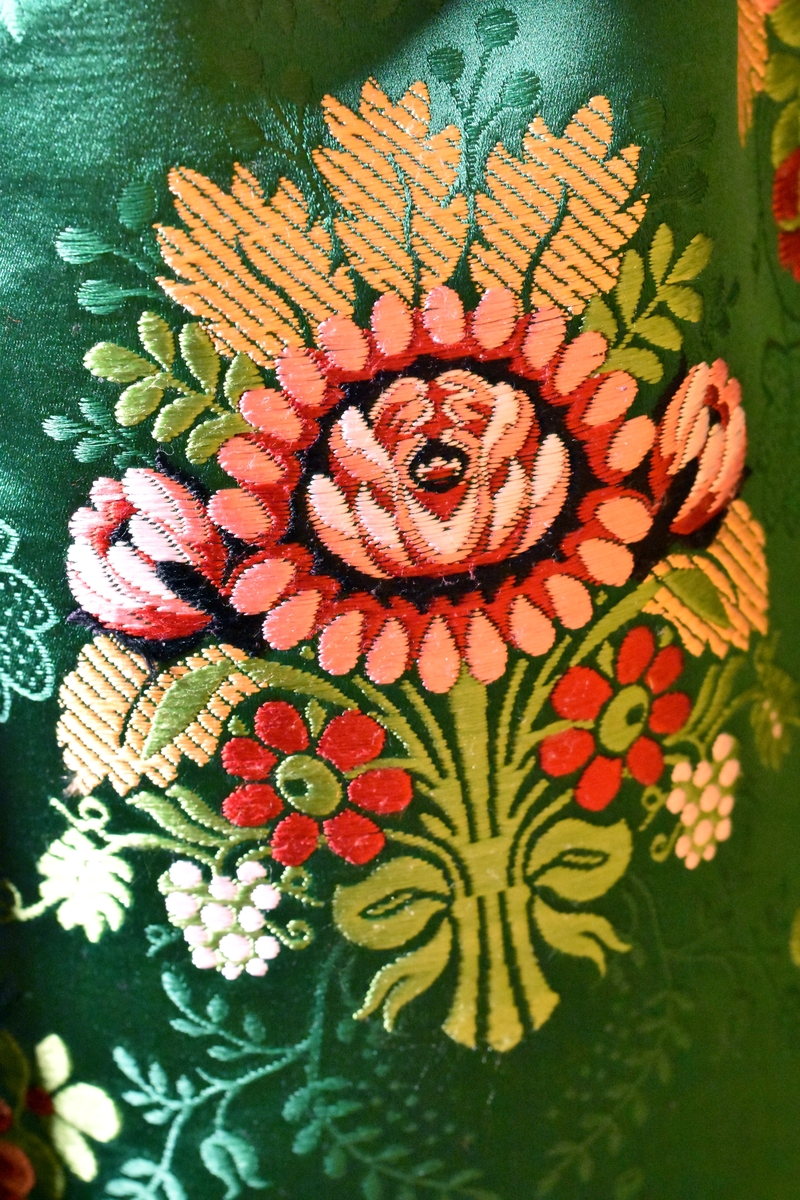 """Förkläde i sidenbrokad, grön botten med stora inplockade rosenbuketter i flotterande silke i rött, rosa, ljusgrönt, vitt och brunt. Upptill dragsko med iträtt grönt sidenband.  Förklädet är skarvat utan mönsterpassning på ena sidan. Kanten är skodd med grönt sidenband från """"Mokuba"""". Skarvarna är sydda på maskin. I övrigt är plagget handsytt."""