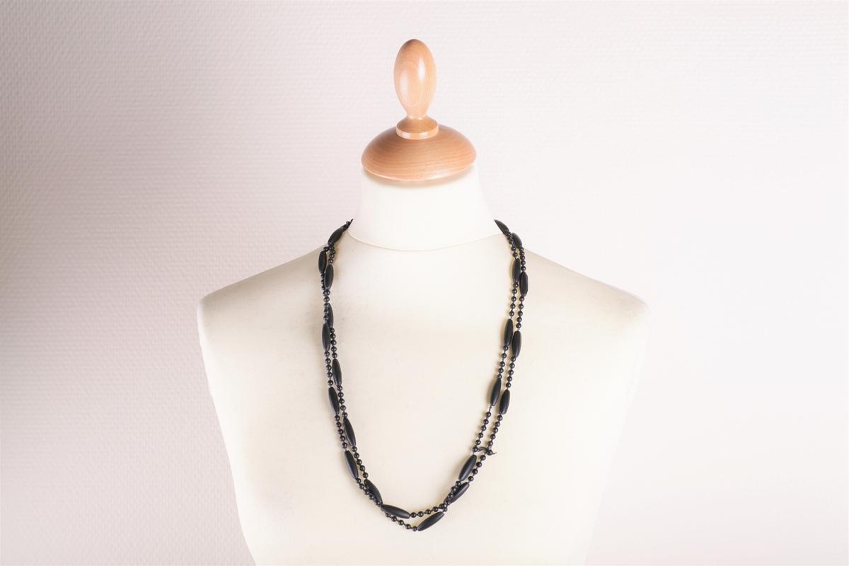 Kjedet består av partier med fem små runde perler og ei avlang perle som gjentas annenhver gang. Tredd inn på ei snor er i alt 26 slike parvis like partier. Svartfarget, og en krok til å henges i. Vakker og elegant utførelse.