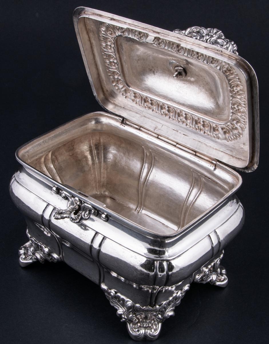 Sockerskrin av silver, fyrsidigt med lock på gångjärn, med nyckel. Uppstående ögleformigt handtag på lockets ovansida. Stämplad: E. G. Öström  G. V4