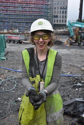 Bildet viser arkeolog Sarah Fawsitt som holder en kanonkule funnet i utgravingsprosjektet B8a