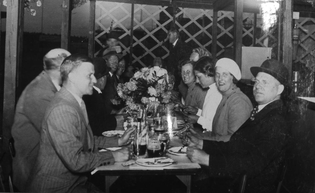Glada middagsgäster under Arbogautställningen. Män och kvinnor som avslutat måltiden på en restaurang. De har dryck kvar i glasen. En stor blomsteruppsättning står på bordet. Den fjärde mannen, i vänstra raden, kan möjligen vara Sven Lind.