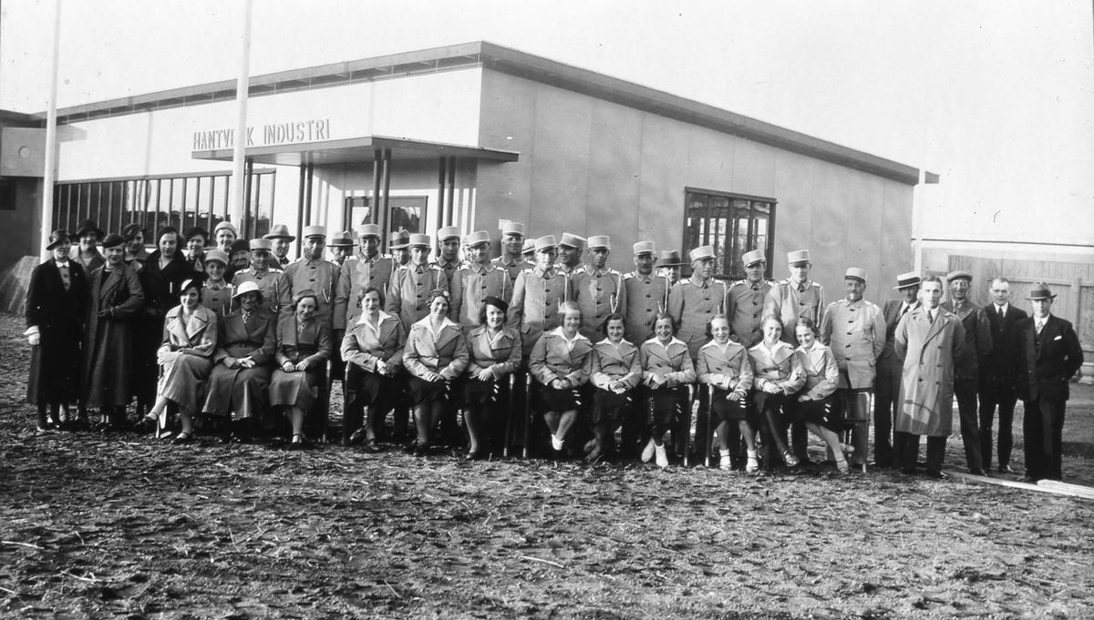 """Gruppfoto av alla lokala funktionärer, under Arbogautställningen, i sina uniformer. De är samlade framför utställningsbyggnaden """"Hantverk Industri"""". Till vänster står några civilklädda kvinnor och till höger en grupp civilklädda män."""