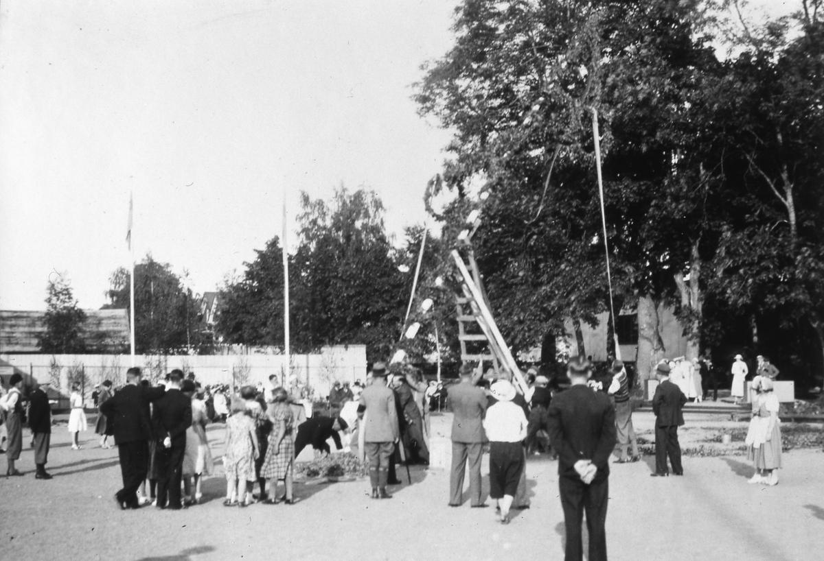 Midsommarstången/Majstången reses på Arbogautställningen. Männen använder stegar. Män, kvinnor, pojkar i äppel-knyckar-byxor och flickor i klänningar ser på. Två kvinnor i servitrisklädsel ses till höger. Flaggorna är hissade. I bakgrunden, till vänster, ses skorstenen vid Arboga Margarinfabrik och tornet på Sankt Nikolai kyrka. (Nicolai) Midsommarfirande