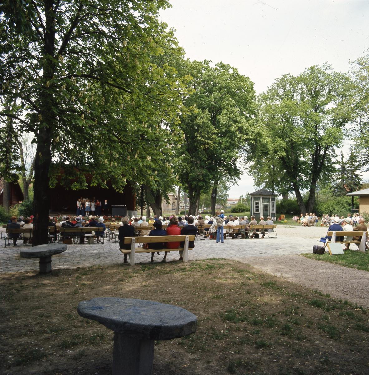 En grupp sångare och gitarrister underhåller på scenen i Olof Ahllöfs park. Publiken är, i huvudsak, äldre människor.