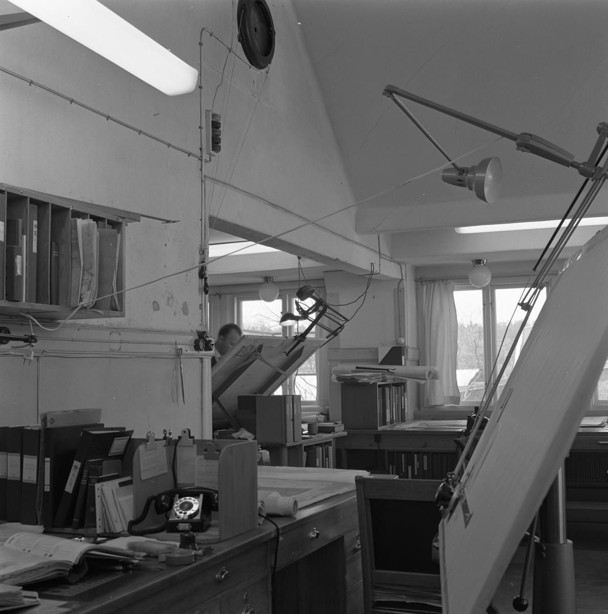 """Man på ritkontoret på """"Meken"""", Arboga Mekaniska Verkstad Interiör från kontoret med ritbord, skrivbord med telefon och hyllor med pärmar."""