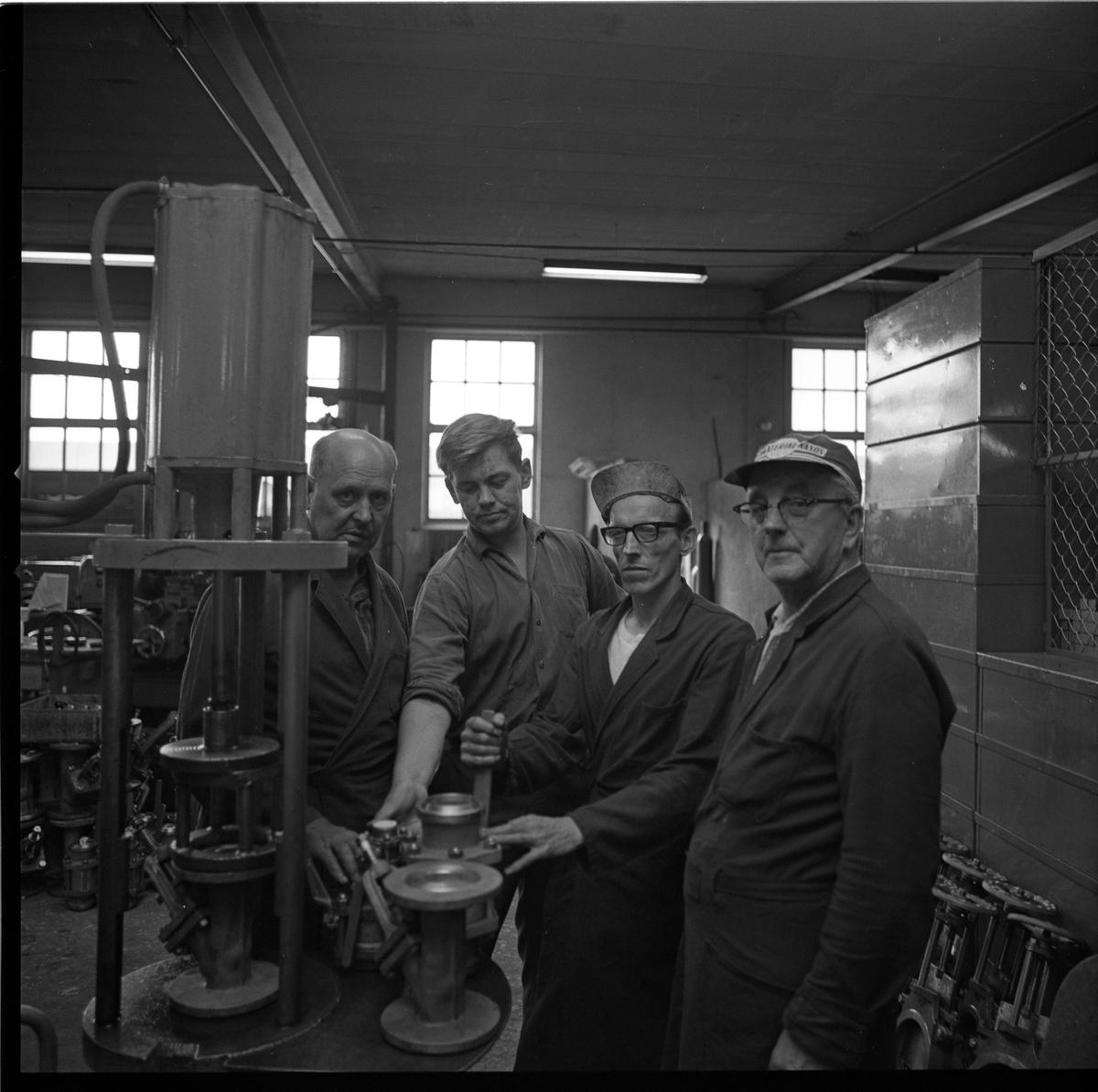 Fyra arbetare på Arboga Armaturfabrik AB. Fabrikslokal, män i arbetsrockar.
