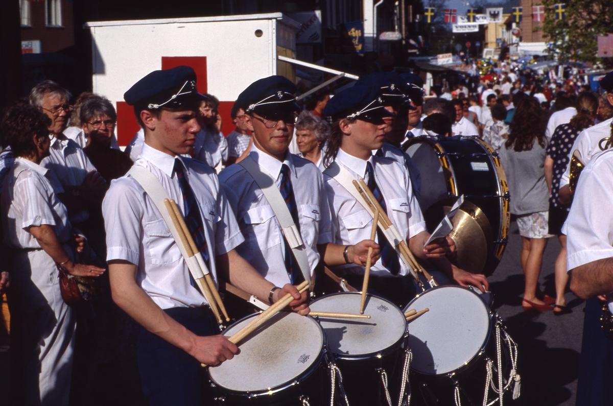 Trumslagare i Arboga Blåsorkester. Orkestern marscherar på Nygatan i samband med marknaden Arbogaträffen. Det är många människor som strosar mellan marknadsstånden.