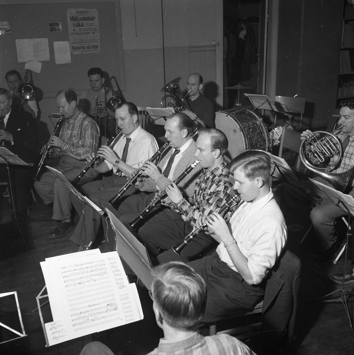 Arboga Blåsorkester repeterar.  Bakre raden, från vänster: okänd (trombon), okänd (trombon), Martin Sköld (trombon) och okänd (valthorn). Främre raden, från vänster:  okänd (klarinett), Herman Fält (klarinett), Karl Rataama (klarinett), okänd (klarinett), okänd (klarinett) och Lars Lennbom (klarinett) Instruktör, för orkestern, är musikdirektör Yngve Kjerrgren, från I 3 Örebro (inte med på bilden)  Män med tromboner och klarinetter, notställ och noter. 1950-talet