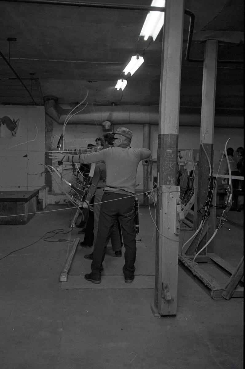 Inomhusträning hos bågskyttarna. Lokalen ser ut att vara i en källare. Skyttarna står uppställda, med pil och båge, och siktar på måltavlor utanför bild. Bakom dem står ställ för bågarna.